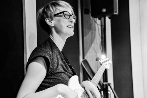 A black and white picture of Ruth playing guitar. It looks like she might be on a stage. She is wearing glasses and a dark top.