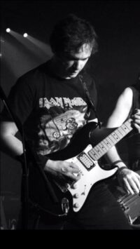A black and white picture of Simon playing guitar. He is wearing an Iron Maiden t-shirt.